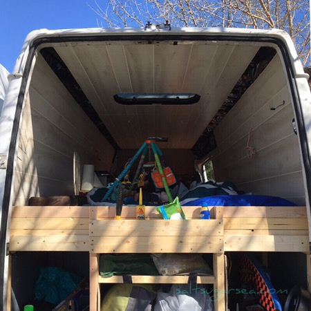 Van Conversion with diy wood bed frame and head board with storage shelf