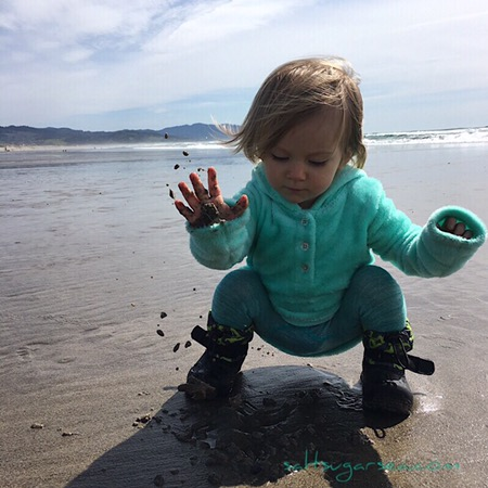 Baby playing in Oregon ocean air and sand