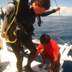 Getting help with the fins topside, Monad Shoal Philippines