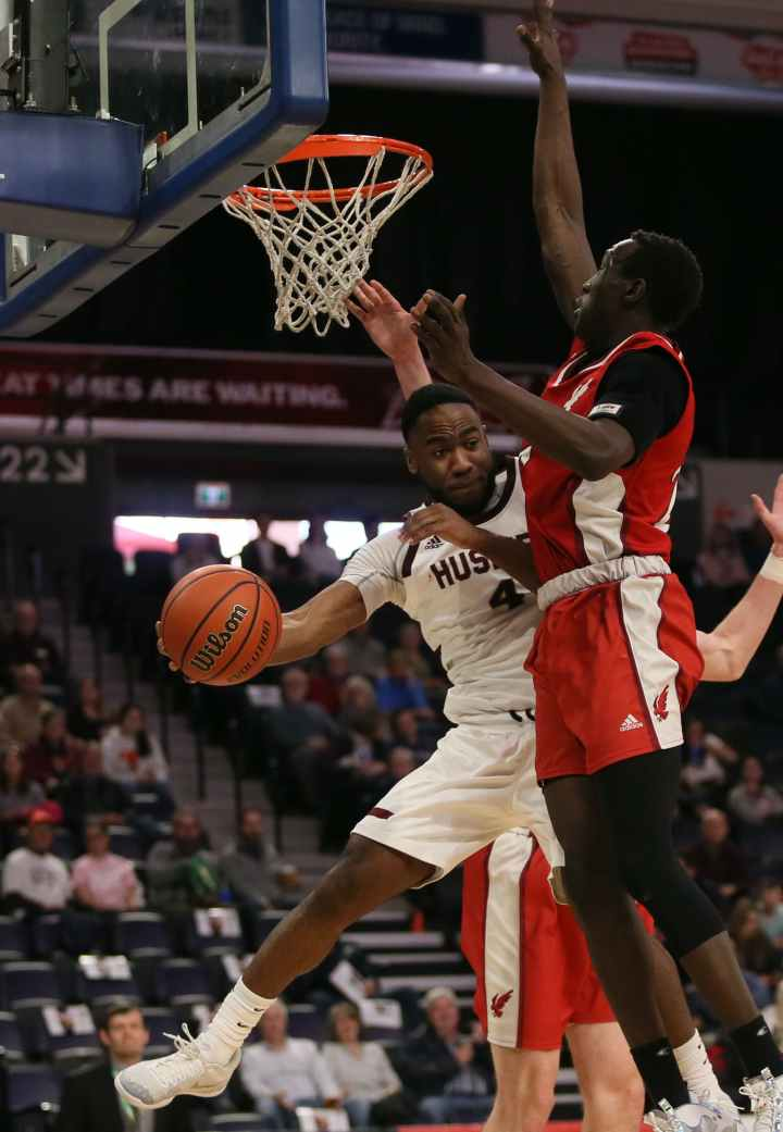 Saint Mary's Huskies guard Johneil Johnson dishes the ball off against the defence of Deng Ring of the Memorial Sea-Hawks during AUS Final 6 quarter-final action at Scotiabank Centre on Friday.  TIM KROCHAK / The Chronicle Herald