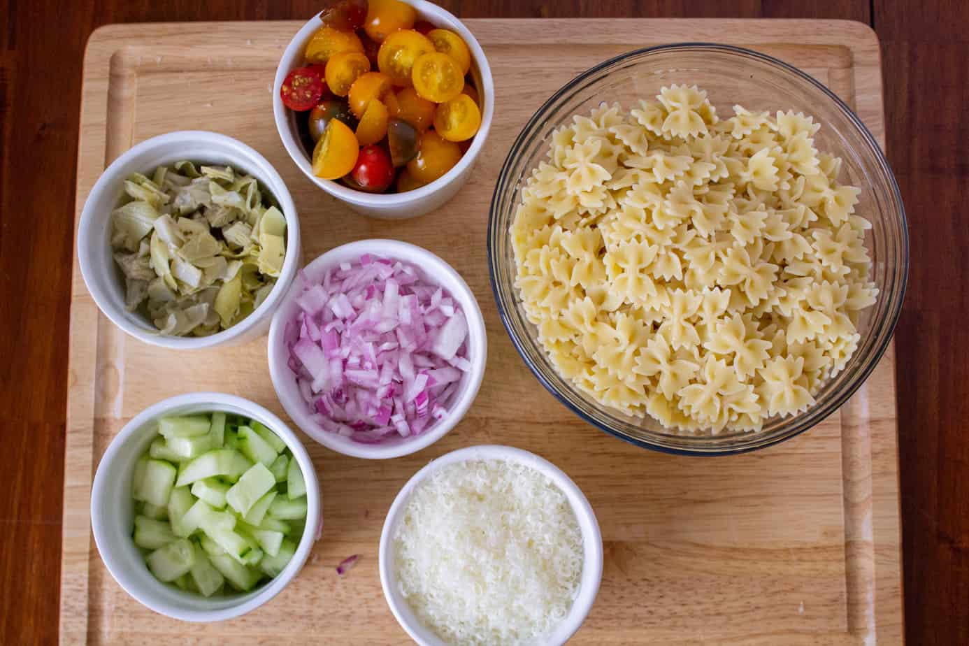 pasta, cherry tomatoes, red onions, parmesan, cucumbers, artichokes in bowls on a cutting board