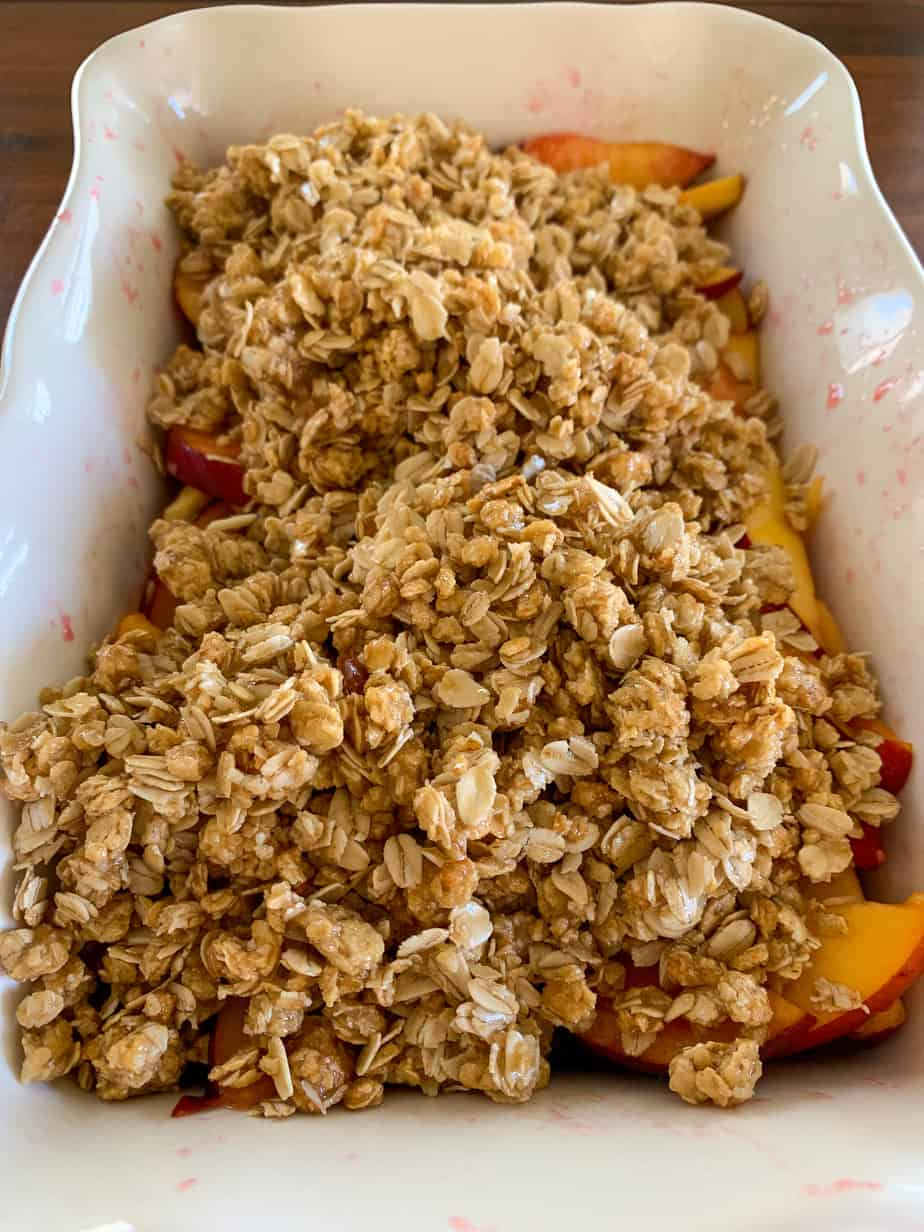 fruit and granola crisp in a white baking dish