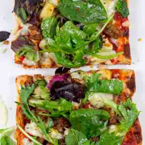 waffle pizza with greens and toppings on a white plate