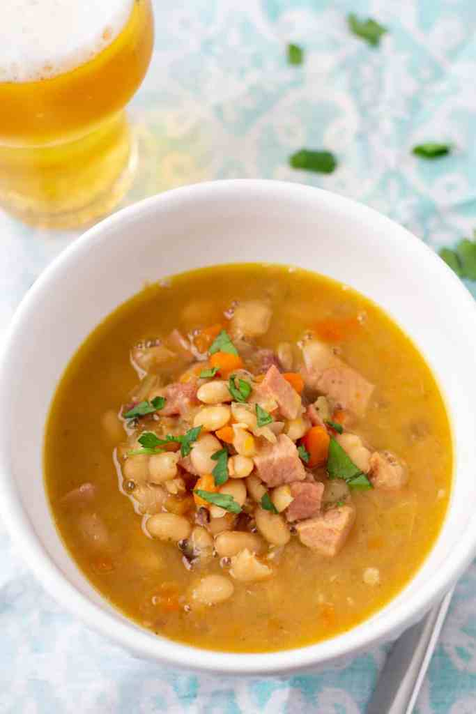 ham and bean soup in a white bowl with a glass of beer to the side