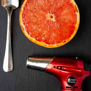 torch, spoon, grapefruit on black background