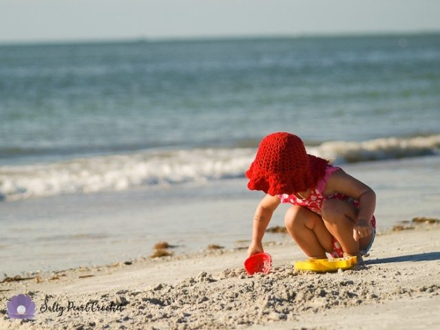 My daughter wearing her Scalloped Toddler Beach Hat while playing in the sand.