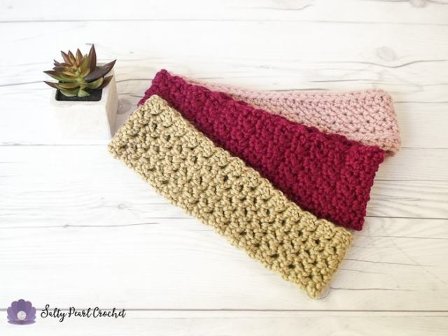 The simple mesh trellis headband laid out on a wooden surface with two of the other headbands featured in the April Flowers Headband Crochet Along.
