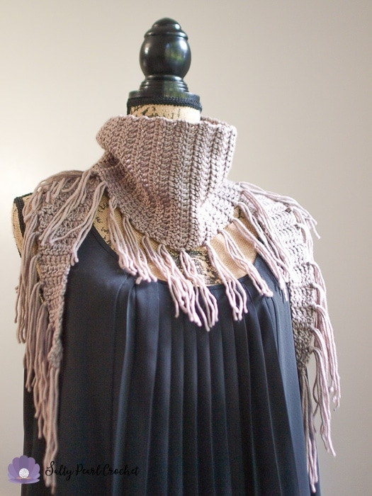 Tight cropped view of this crochet triangle scarf with fringe on a mannequin.