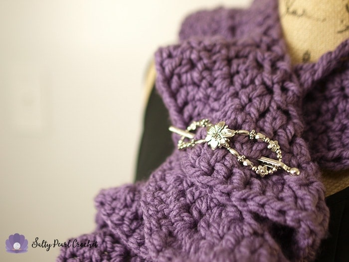 Closeup of the shawl pin securing the chunky crochet ruffle scarf.