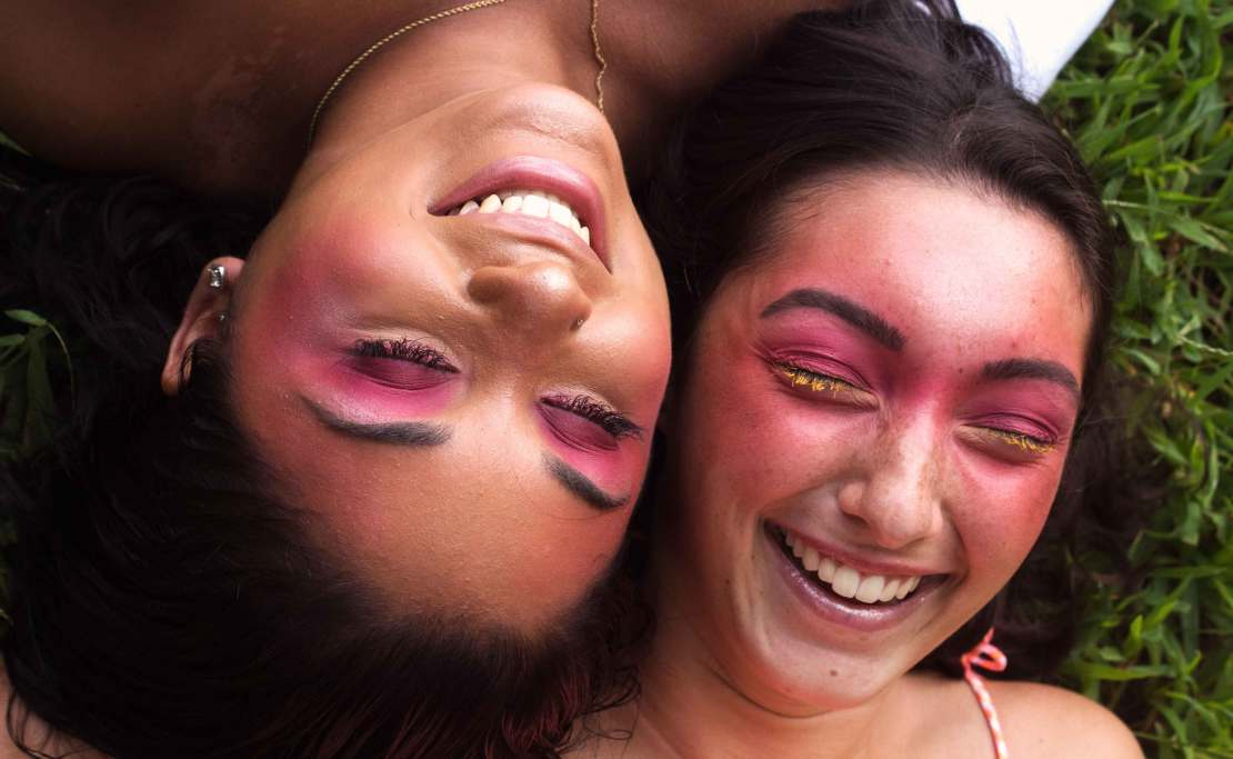 close-up of two people with colorful makeup, laughing and laying in the grass