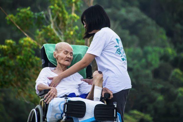 Mujer cuidando a un anciano enfermo en una silla de ruedas