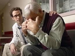 Médico dando una mala noticia a un anciano que se tapa la cara