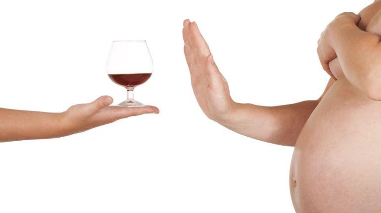 Embarazada rechazando copa de vino.