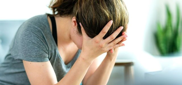 Mujer con la cabeza agachada y las manos en la cara. Está sufriendo