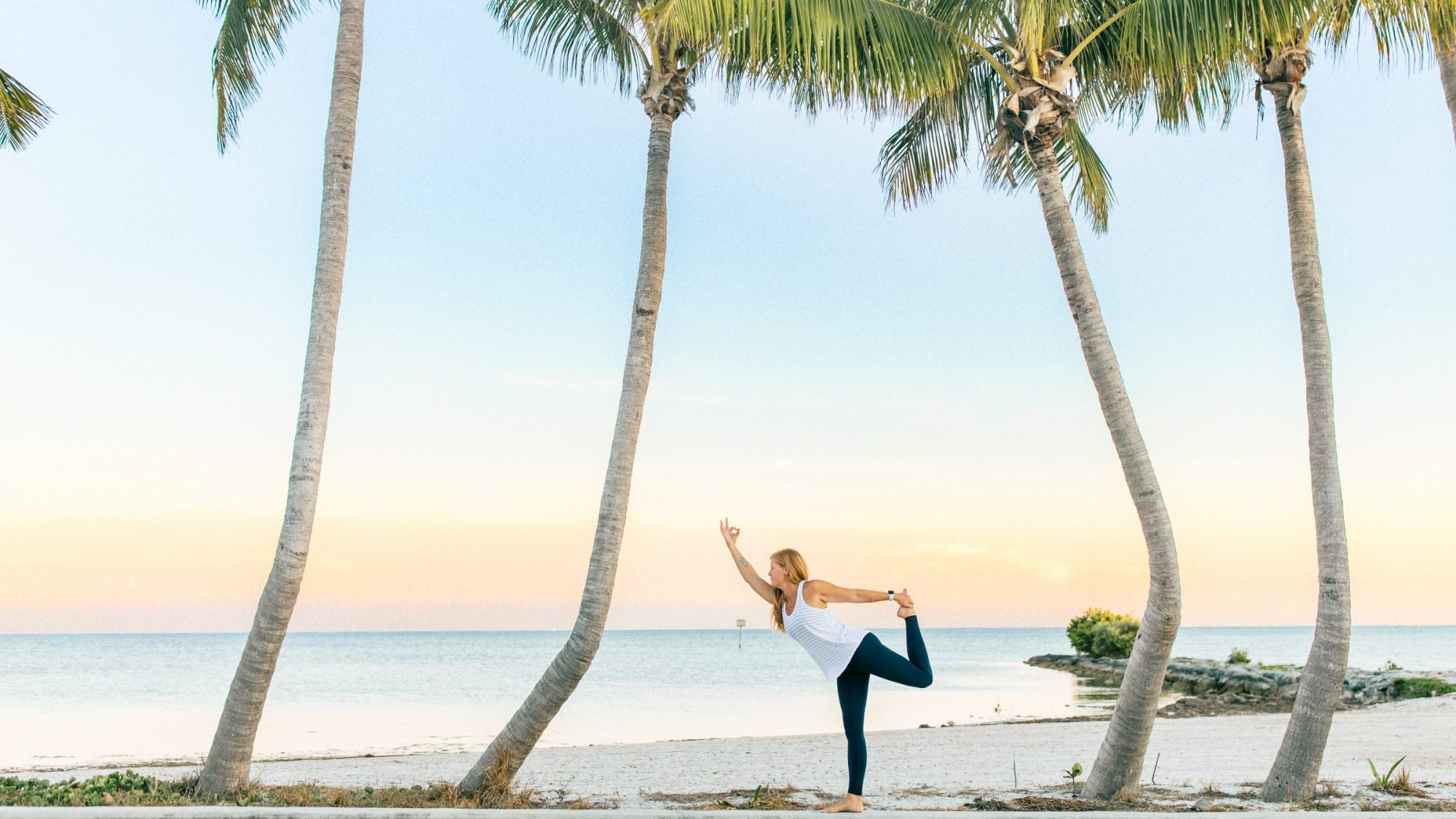woman doing a yoga pose under palm trees