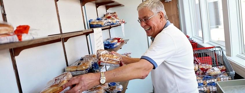 volunteer stocking shelves at TSA food pantry