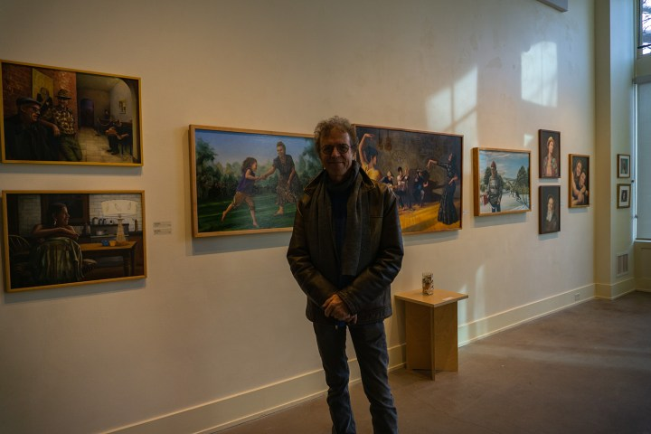Sam Albright in front of paintings on gallery wall