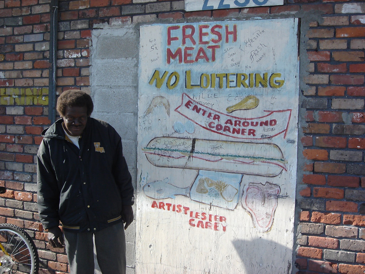 Lester Carey next to a hand-painted sign