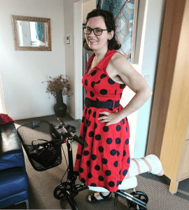 sammy on a knee walker in a red lady bug dress from review