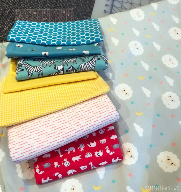 stack of fabrics for yellow, blue, red, gray triangle baby quilt
