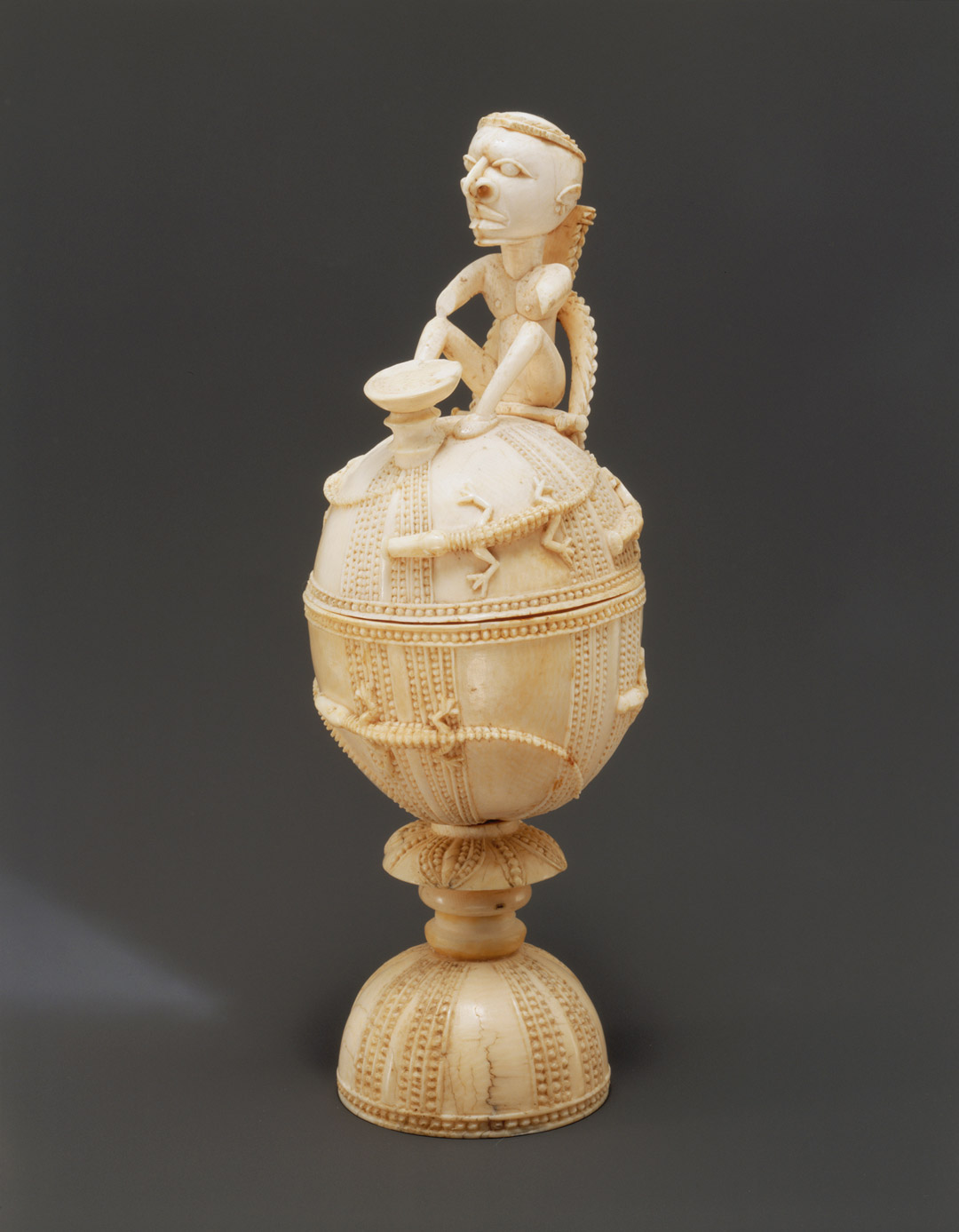 A photograph of a intricately carved salt cellar with a figure sitting on top of a round shape with a crocodile motif wrapping around the base.