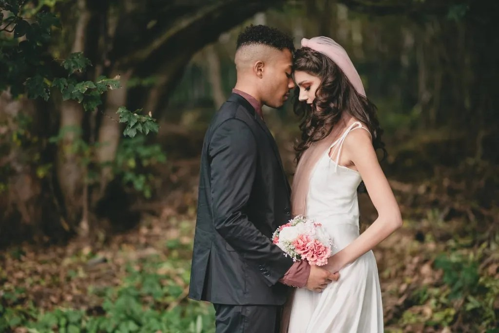 Bride and Groom share a tender moment whilst taking photos with their wedding photographer