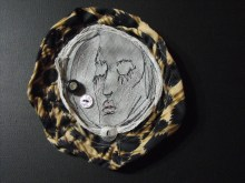 Textile brooch with sewn portraits.