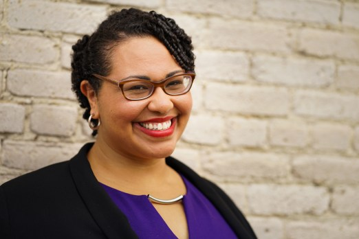 Medium shot of Dr. Sami Schalk. She is a light-skinned black woman with short curly hair and brown glasses. She is smiling to the camera in front of an off-white painted brick wall. She is wearing a black jacket over a purple dress, red lipstick and silver hoop earrings.