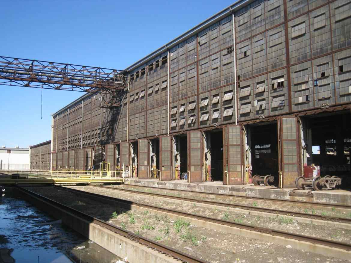 An image of an old and abandoned train station along the water, with a rusted walkway going across.