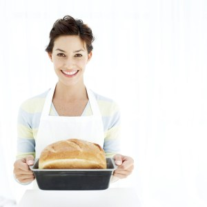 Woman Holding a Baking Tray with Freshly Baked Bread --- Image by © Royalty-Free/Corbis