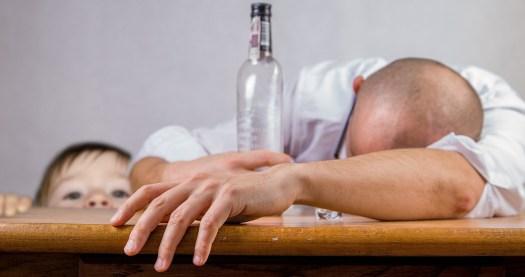 pijany mężczyzna leży na stole, a obok jest dziecko jako symbol zaniedbanie