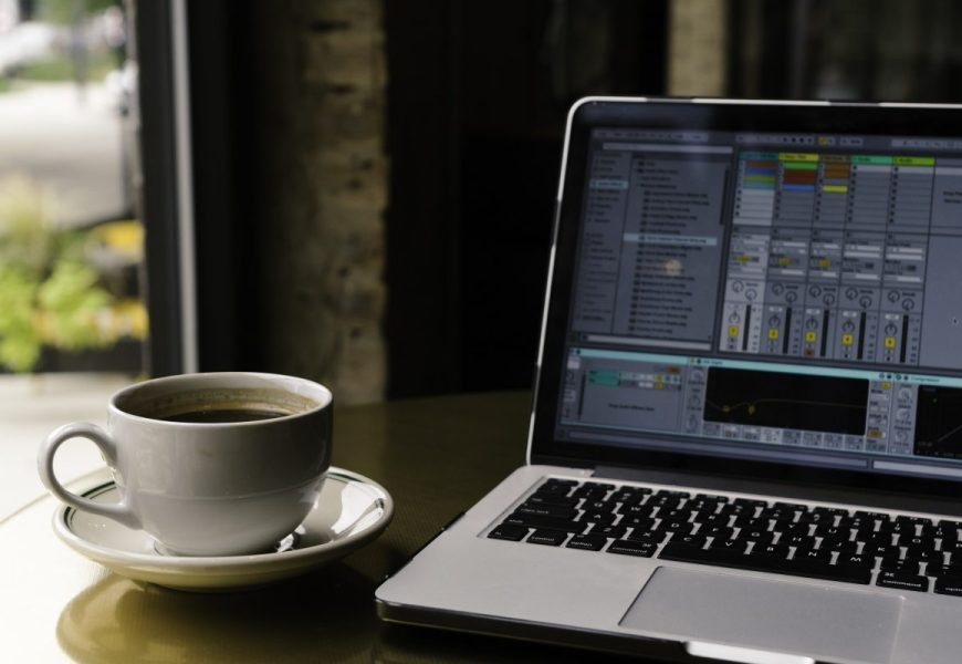 Ableton Live on a laptop with a cup of coffee