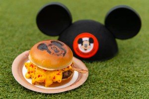 Mickey Cheeseburger – Angus burger with macaroni and cheese, American cheese, cheese sauce, and spicy cheese dust on a Mickey Mouse Bun; available at Cosmic Ray's Starlight Cafe