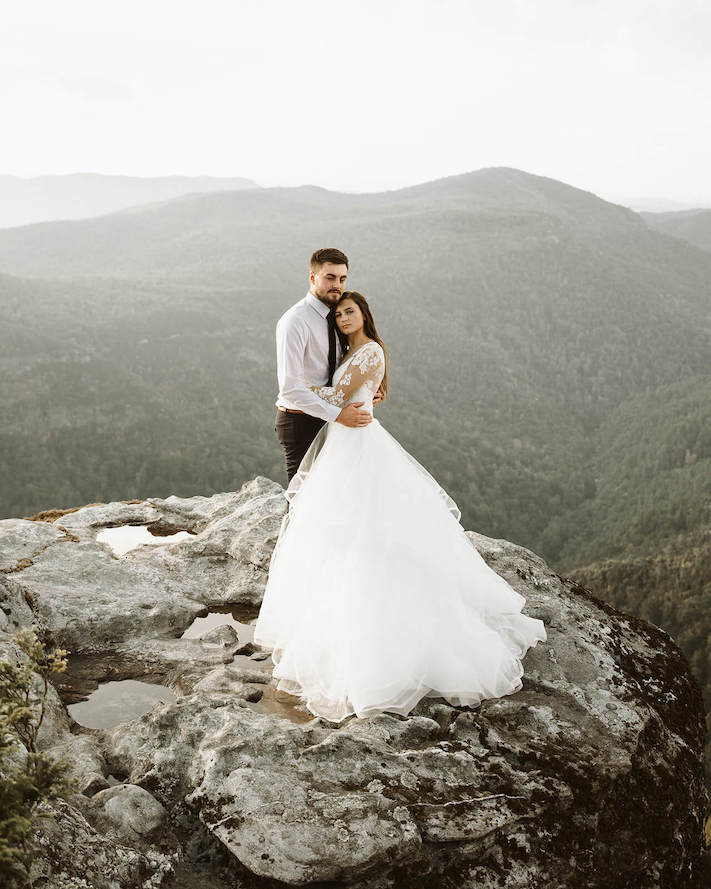 couple hugging on top of a big boulder near asheville