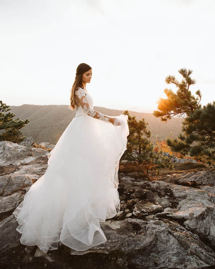 holding wedding dress as the sun sets