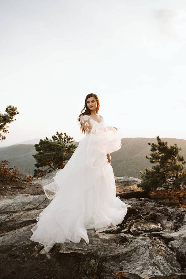 wind blowing white dress as bride holds it