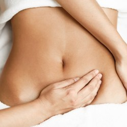 Top view of hands massaging female abdomen.Therapist applying pressure on belly. Woman receiving massage at spa salon
