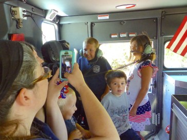 Children of firefighters test the sound system in Engine 165.