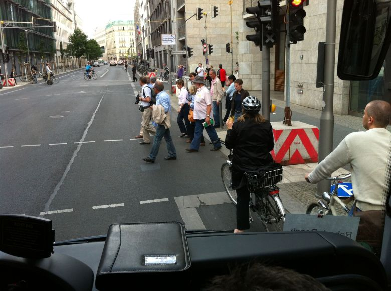 The view from a bus: Vehicles, cyclists, and pedestrians share the street.