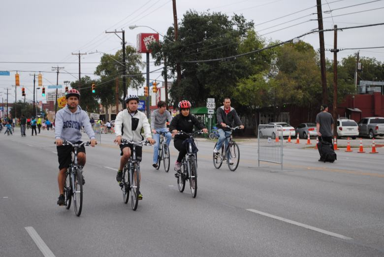 A group of guys ride together down streets closed off to traffic.
