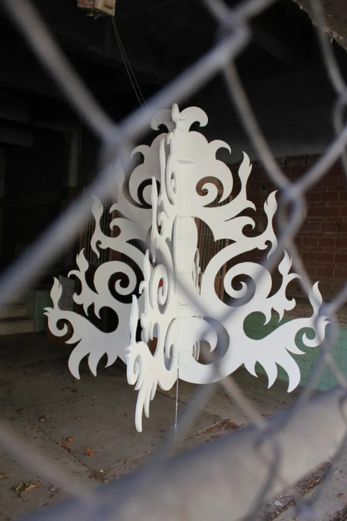 "The elegance of Sage Gibson's ""Chandelier on Steroids"" stands in stark contrast to the chain link fence that surrounds it. (205 N St. Mary's St.) Photo by Melanie Robinson."