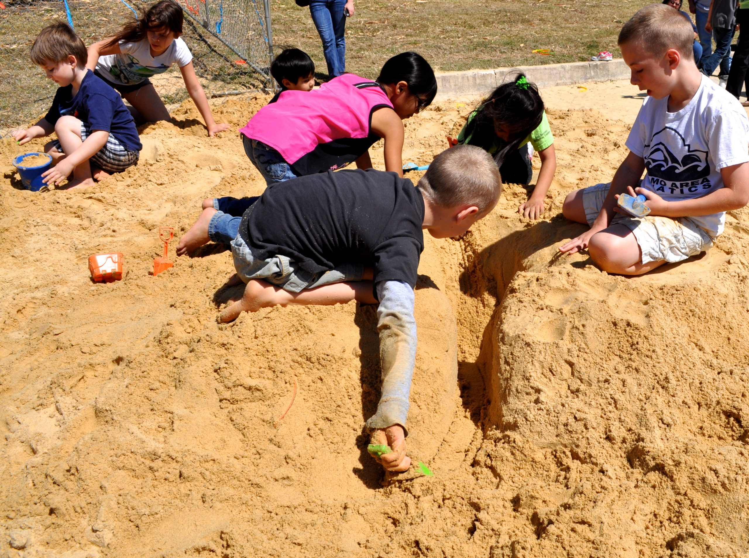 A group of children work to dig the deepest hole in the sand without collapsing in the sides. The project's forman (right), led his team effectively to achieve that goal. Photo by Iris Dimmick.