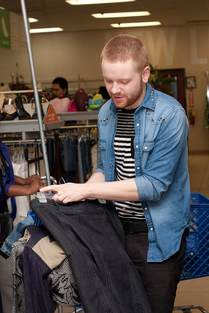 Adison Chase sorts through clothes at Goodwill. He is one of 12 designers competing to win the Thrift Off SA challenge. Photo by Sean Davis Photography.