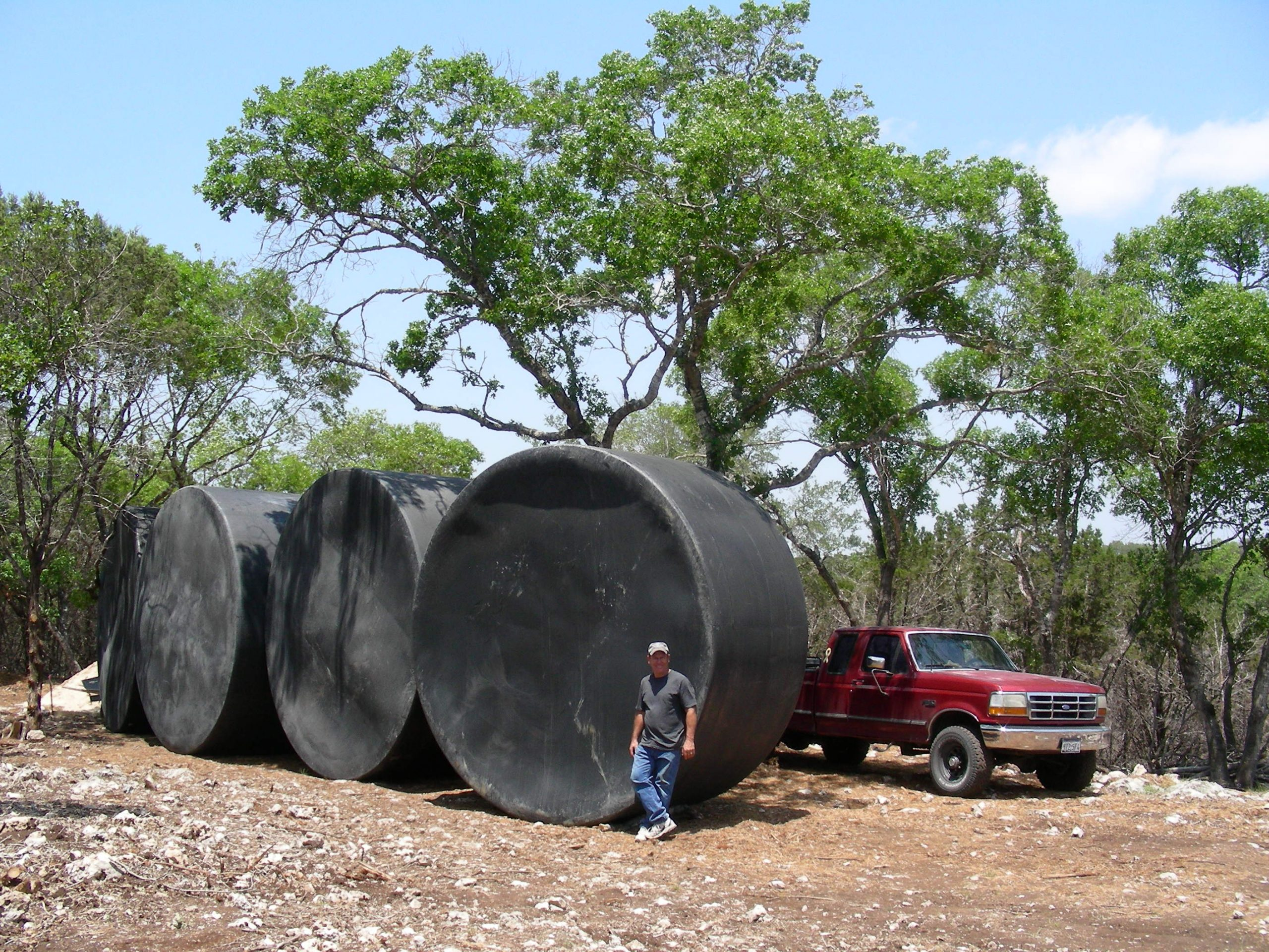 The four 5,000 gallon storage tanks that form the core of a residential rainwater harvesting system. Photo by Andrew Michalec