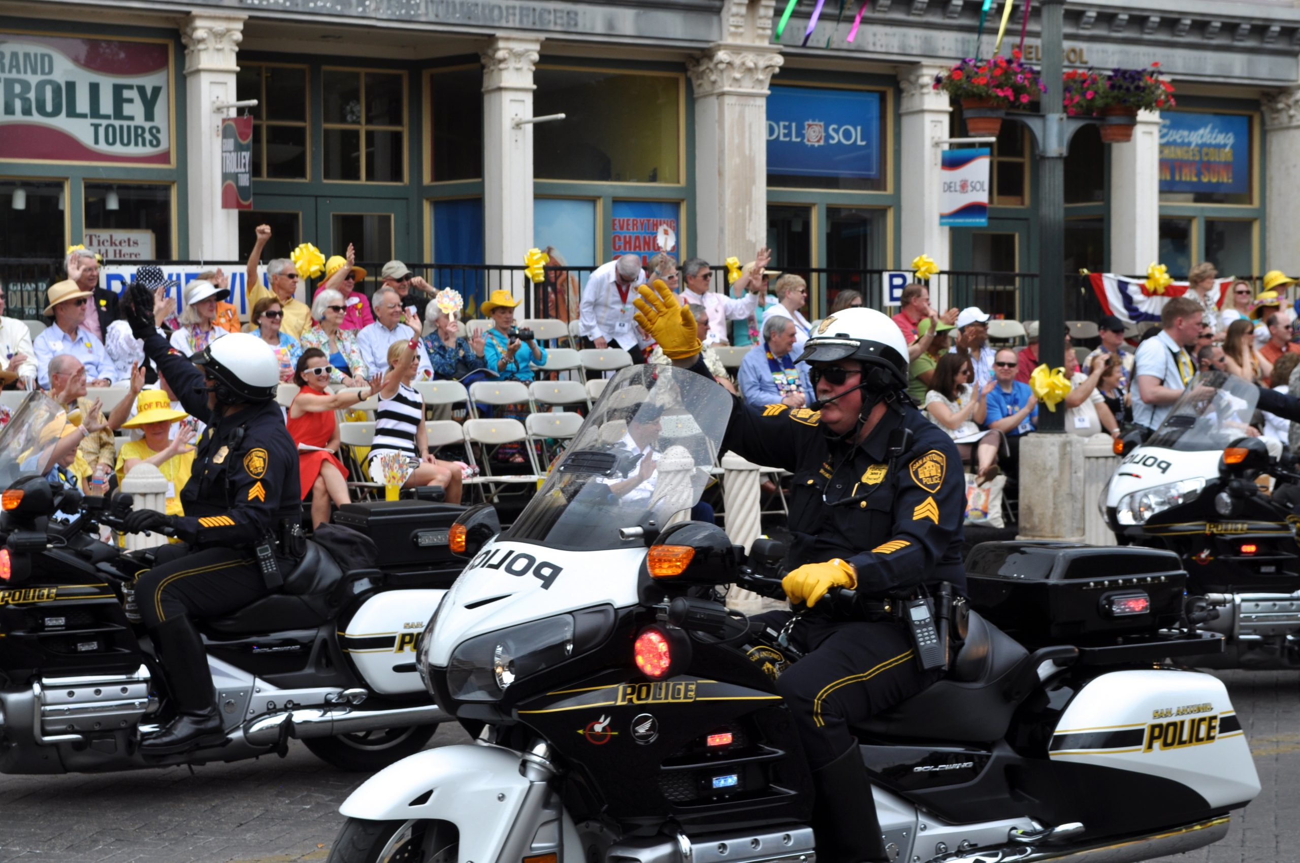 Officers of the San Antonio Police Department Motorcycle Unit wave at the thronging crowds at Alamo Plaza during the Battle of the Flowers parade (2013). Photo by Iris Dimmick.