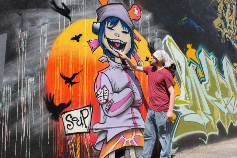 """Gallery owner """"Soup"""" describes his newest creation on the back wall of The Paintyard. Photo by Melanie Robinson."""