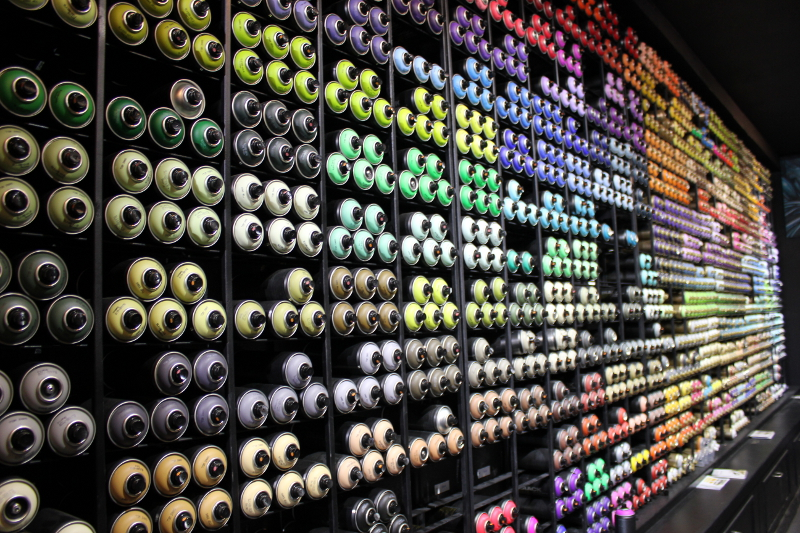 Walls of aerosol line the inside of the shop many graffitti artists call home. Photo by Melanie Robinson.