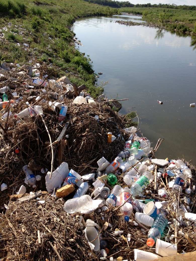 A river runs through it: Fiesta garbage litters the Mission Reach of the San Antonio River. Photo by Robert Rivard