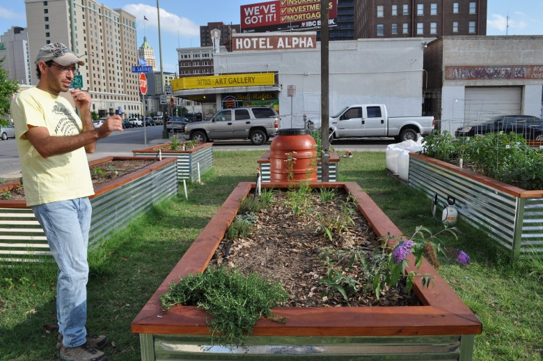 Steve Flannery explains that  by raising the gardening beds, plants are able to retain more nutrients while avoiding erosion of the existing land. Photo by Iris Dimmick.