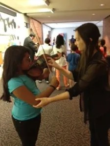 "Alysson Salazar, 10, from Heartman Elementary ""pets"" a violin with a YOSA member, who guides her. Photo courtesy of YOSA."